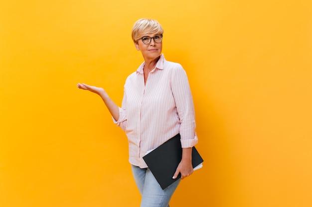 La donna premurosa in camicia rosa e occhiali da vista pone con i documenti