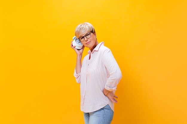 Thoughtful woman in pink shirt listens to alarm clock on orange background