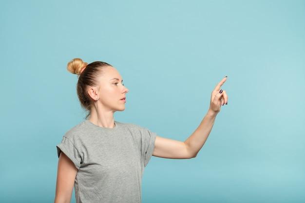 Заботливая женщина, достигнув, чтобы нажать невидимую кнопку на синем. интерфейс или концепция виртуального экрана.