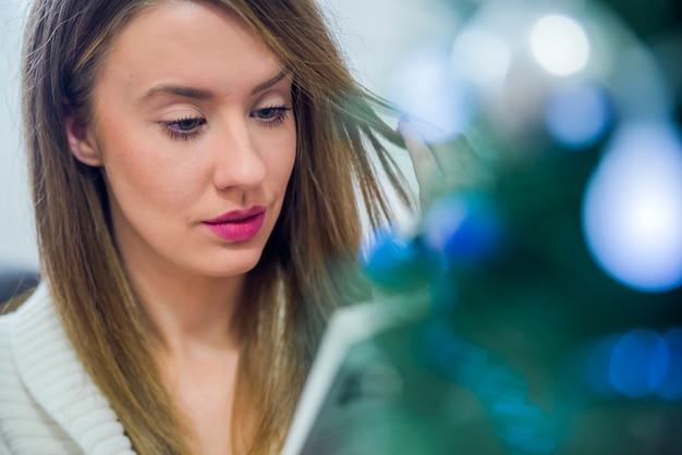 Задумчивый женщина, чтение книги в рождество украшен дома. концепция праздника, рождество, праздники и люди