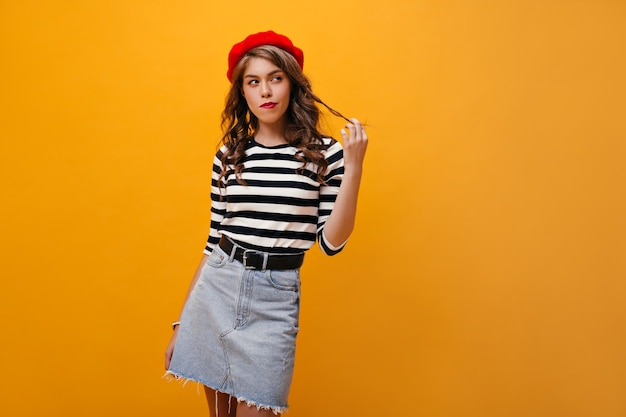 Donna premurosa in berretto rosso che tocca i suoi capelli. bella ragazza con capelli ondulati in gonna di jeans con cintura nera in posa su sfondo arancione.