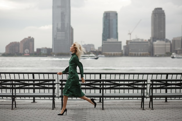 Thoughtful woman runs in her elegant dress along the river shore in new york