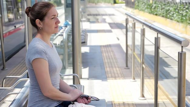 사려 깊은 여자는 더운 날 폐쇄된 마차 문 정류장 맞은편에 트램카가 도착하기를 기다리는 벤치에 반쪽 얼굴을 앉습니다