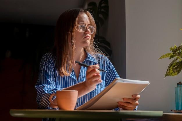 카페 테이블에 앉아 창을 통해 글을 쓰고 계획에 대해 생각하는 사려깊은 여성