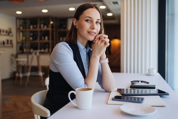 コーヒーマグとカフェテリアに座っている思いやりのある女性。考えながらお茶を飲む中年女性。コーヒーを飲みながらリラックスして考えます。