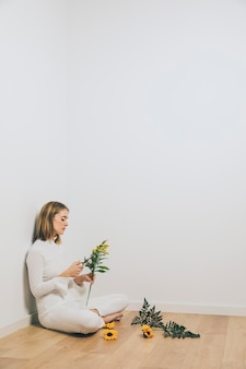 Thoughtful woman sitting with plant branches