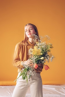 Thoughtful woman standing with flowers bouquet