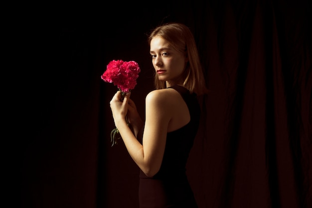Thoughtful woman standing with pink flowers