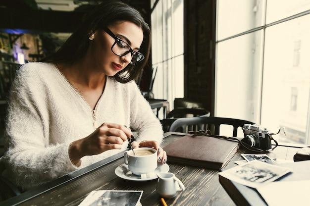 思いやりのある女性はコーヒーのカップで砂糖をかき混ぜる