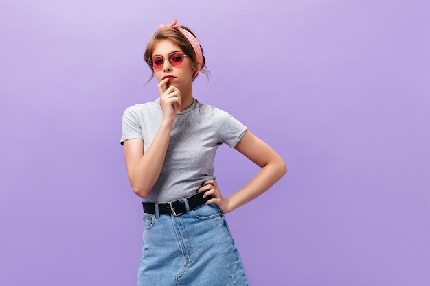 Thoughtful woman in sunglasses and grey shirt poses on purple background. pretty young lady in pink headband and summer clothes looking into camera.