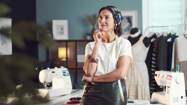 Задумчивая женщина-портной оперлась на стол, стоящий в швейной мастерской