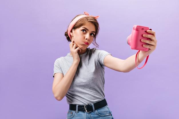 思いやりのある女性は紫色の背景で自分撮りを取ります。ピンクのヘッドバンド、グレーのtシャツ、流行のスカートを着たクールな若い女の子が写真を作ります。