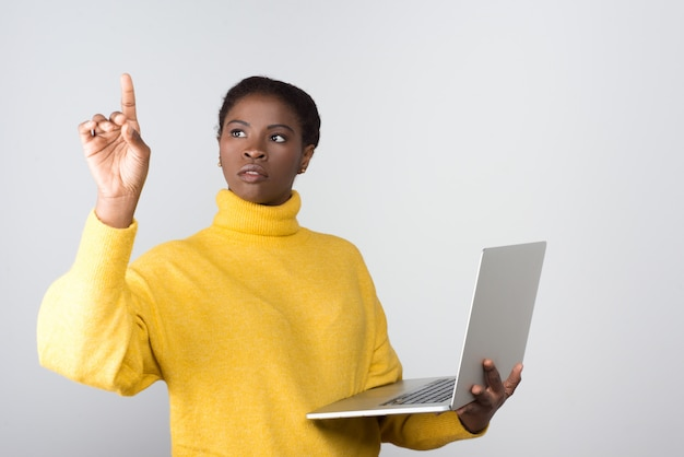 Thoughtful woman touching virtual screen and holding laptop
