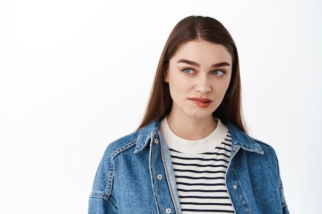 Задумчивая женщина чего-то сильно хочет, прикусывает нижнюю губу и смотрит в сторону на рекламное пространство текста, желание, желание попробовать, стоит над белой стеной