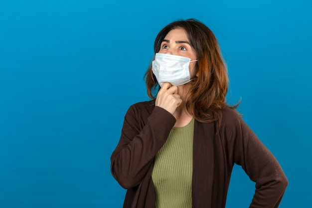 Thoughtful woman wearing brown cardigan in medical protective mask standing with hand on chin looking up thinking over isolated blue wall