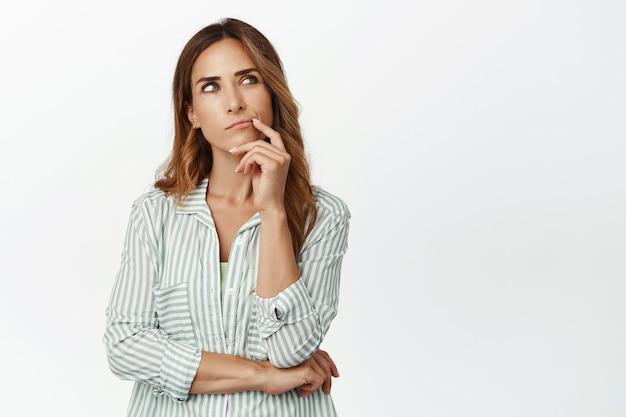 Donna premurosa, moglie che pensa, alzando lo sguardo e toccando il labbro, meditando su una decisione importante, facendo una scelta, in piedi in camicetta contro il muro bianco