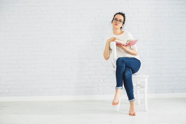 Thoughtful woman with book on chair