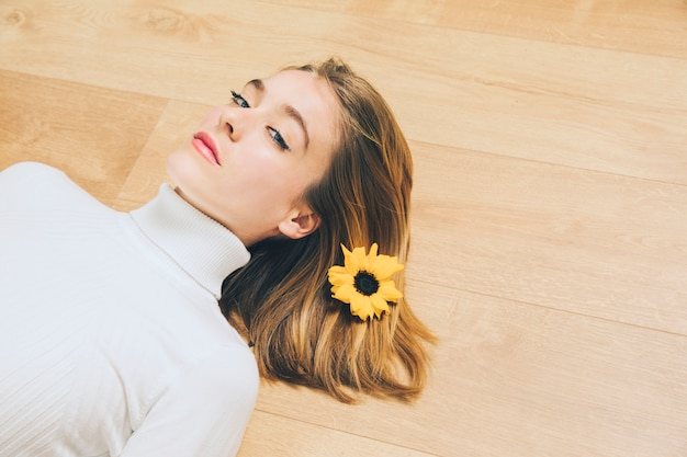 Thoughtful woman with bright flower in hair lying on floor