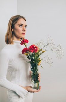 Thoughtful woman with bright flowers in vase at wall