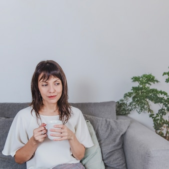 Thoughtful woman with coffee on sofa