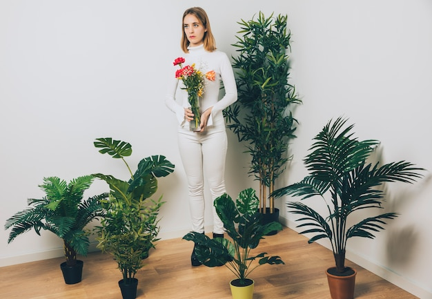 Thoughtful woman with flowers in vase near green plant