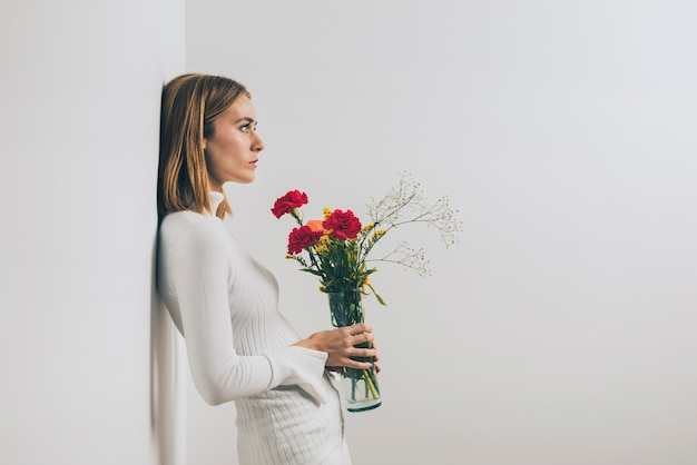 Thoughtful woman with flowers in vase at wall