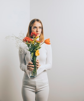 Thoughtful woman with flowers in vase