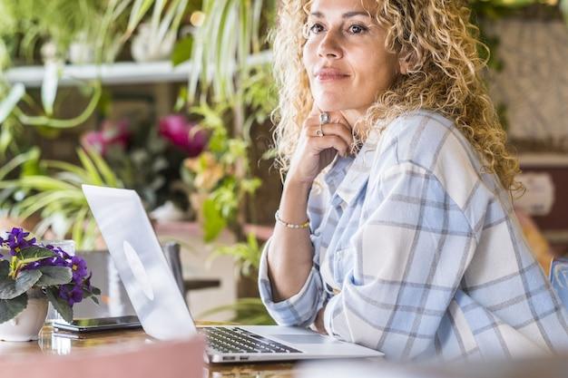 屋外レストランのテーブルにノートパソコンと携帯電話を持つ思いやりのある女性。カフェやレストランで思いを馳せた巻き毛の美女。カフェで余暇を過ごす女性