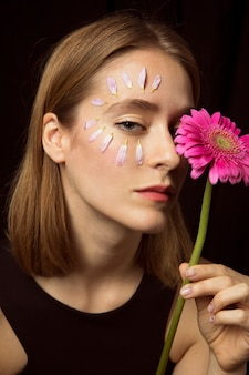 Thoughtful woman with petals on face and gerbera