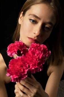Thoughtful woman with pink carnations