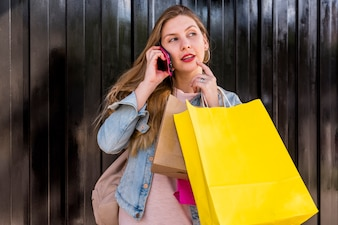 Thoughtful woman with shopping bags talking by phone