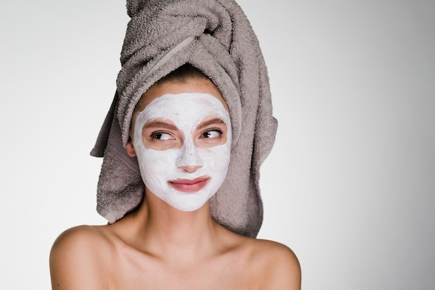 A thoughtful woman with a towel on her head after a shower put on her face mask