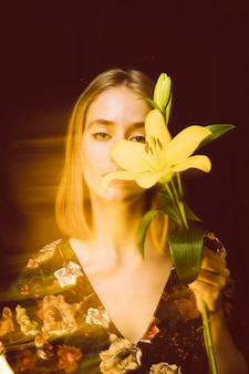 Thoughtful woman with yellow flower