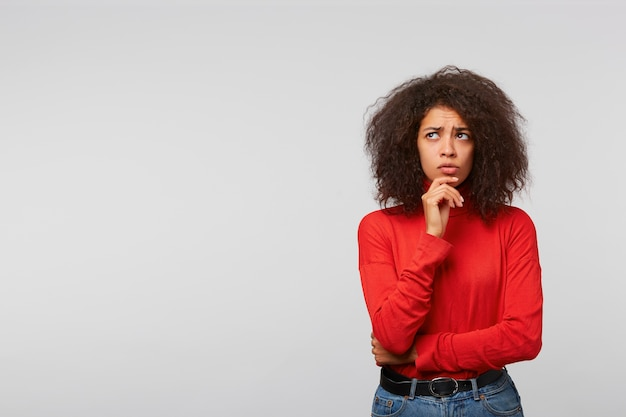 Thoughtful worried young woman with afro hairstyle, looks to the upper left corner at blank copy space, keeps fist near chinwall