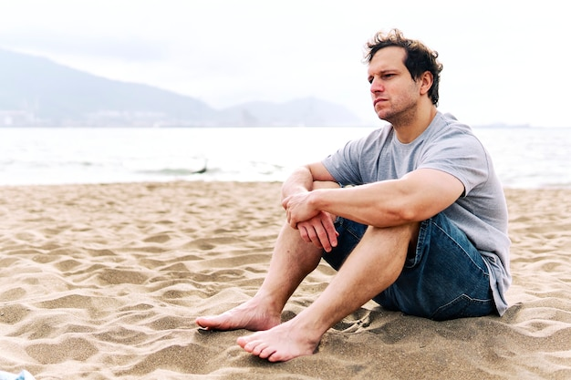 Thoughtful young adult man sitting on the beach sand with melancholic gesture