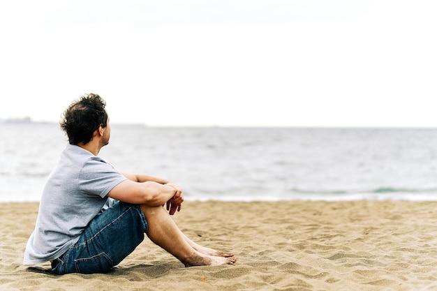 우울한 몸짓으로 해변 모래에 앉아 사려깊은 젊은 성인 남자