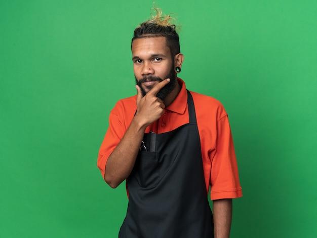 Задумчивый молодой афро-американский парикмахер-мужчина в униформе держит руку на подбородке, изолированную на зеленой стене с копией пространства