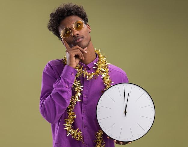 Задумчивый молодой афро-американский мужчина в очках с гирляндой из мишуры на шее держит часы, держа руку на подбородке, глядя в сторону, изолированную на оливково-зеленом фоне