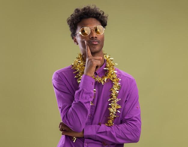Riflessivo giovane afro-americano con gli occhiali con tinsel garland intorno al collo guardando il lato toccando la faccia isolata su sfondo verde oliva