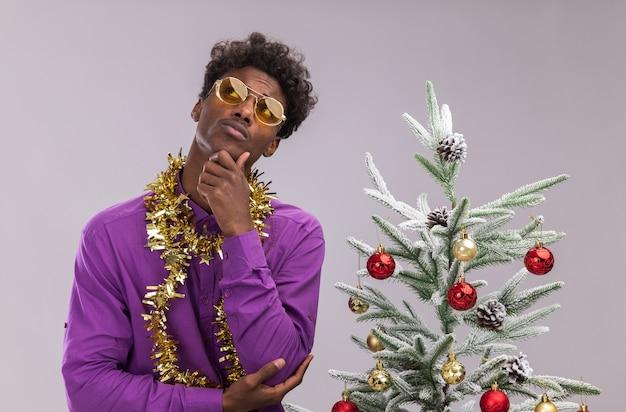 Riflessivo giovane afro-americano con gli occhiali con la ghirlanda di orpelli intorno al collo in piedi vicino all'albero di natale decorato tenendo la mano sul mento cercando isolato su sfondo bianco