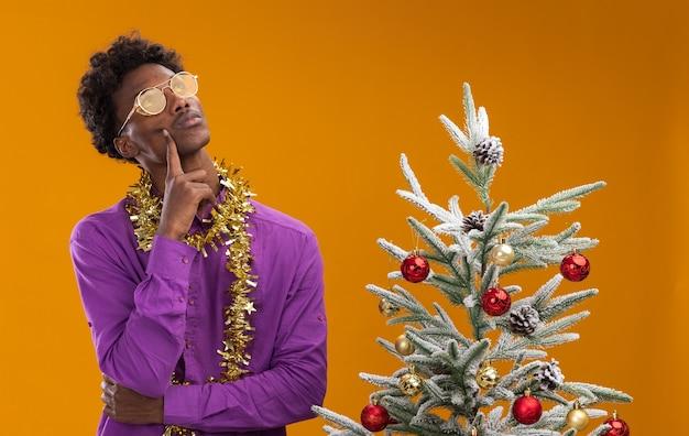 주황색 배경에 장식 된 크리스마스 트리 근처에 서있는 목 주위에 반짝이 갈 랜드와 안경을 쓰고 사려 깊은 젊은 아프리카 계 미국인 남자