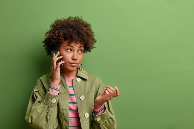 Thoughtful young afro american woman raises hand has telephone conversation considers information heard from interlocutor wears stylish clothes isolated over vivid green wall