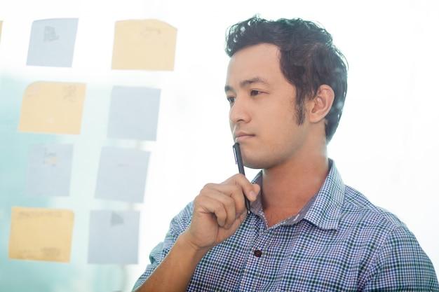 Продуманный молодых азиатских деловой человек планирование работы