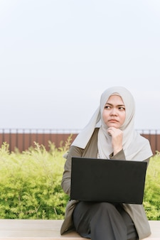 Thoughtful young asian muslim woman in green suit and working on a computer at park. hand near the face.