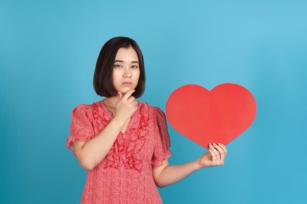Thoughtful young asian woman in a red dress holds a large red paper heart and touches her chin