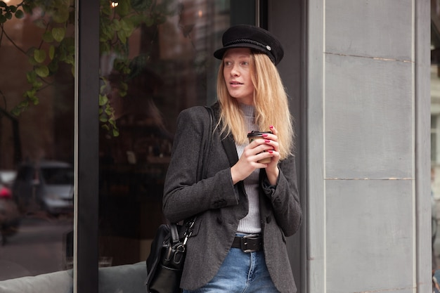 Giovane donna attraente premurosa con capelli lunghi biondi che beve caffè mentre cammina all'aperto e guarda pensieroso da parte, vestita di cappello e cappotto nero