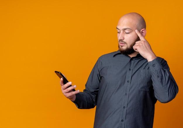 Задумчивый молодой лысый человек из колл-центра, держащий и смотрящий на мобильный телефон, кладет палец на висок, изолированный на оранжевой стене