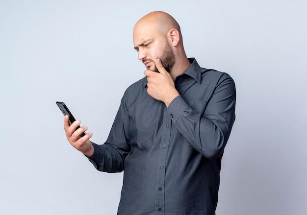 Uomo calvo giovane premuroso della call center che tiene e che esamina il telefono cellulare con la mano sul mento isolato sulla parete bianca
