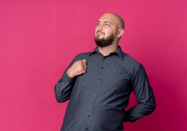 Thoughtful young bald call center man keeping hand behind back looking at side and keeping fist on chest isolated on crimson wall