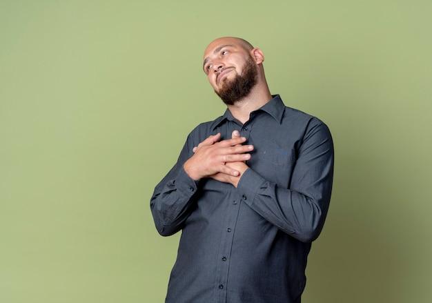 올리브 녹색 벽에 고립 된 가슴에 손으로 똑바로 찾고 사려 깊은 젊은 대머리 콜 센터 남자